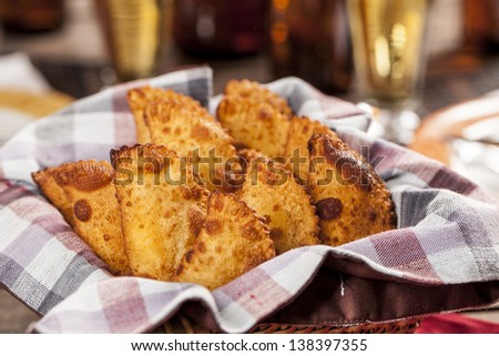 Pastel, a Brazilian snack, with a bar in the background. - stock photo