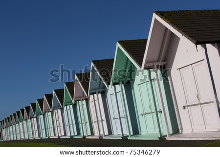 Pastel Beach Huts A row of beach huts tapering off into the distance pastel colored with a deep blue sky above - stock photo