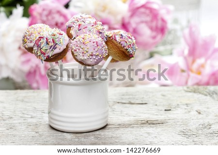 Pastel cake pops on rustic wooden table. Stunning peony flowers in the background. - stock photo