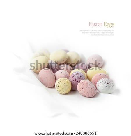 Pastel candy coated chocolate Easter eggs on a white background. Copy space. - stock photo