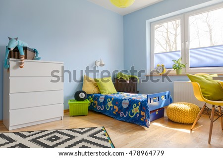 Pastel child room with a chest of drawer, bed, pouf and big window