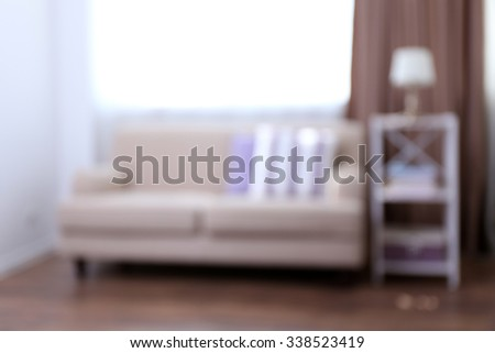 Pastel color room interior with comfortable sofa and pillows, blurred