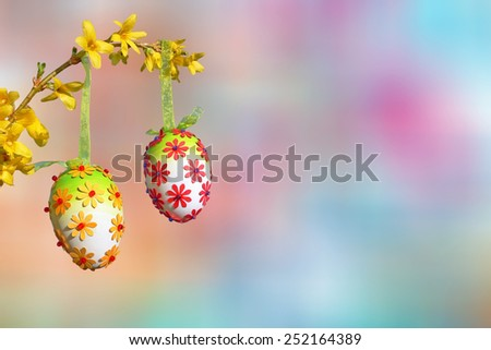 pastel colored background, forsythia branch with blossoms and group of handmade easter eggs - stock photo