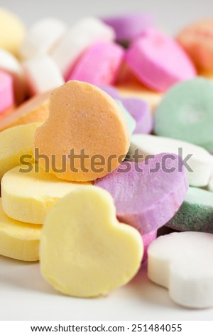 Pastel colored candy hearts in a pile on a white surface. - stock photo