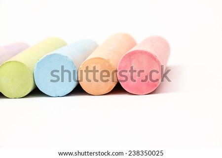 Pastel colored chalk sticks on a white background - stock photo