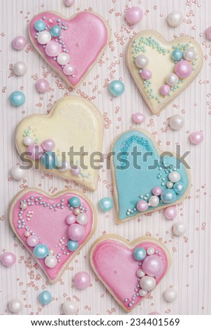 Pastel colored heart shaped cookies on a wooden background - stock photo