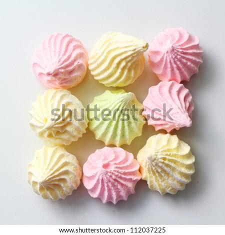 Pastel colored meringue on white background - stock photo