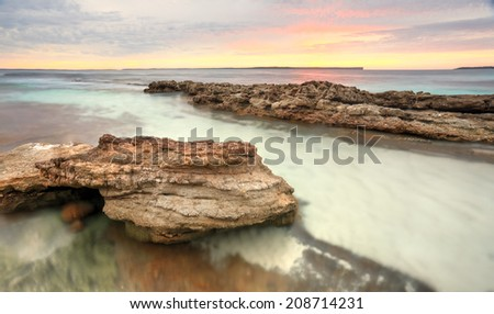 Pastel colours of a surreal sunrise at Hyams Beach at Jervis Bay, Australia.  Long exposure - stock photo