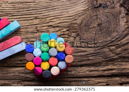 Pastel crayons and pigment dust on old wooden background - stock photo