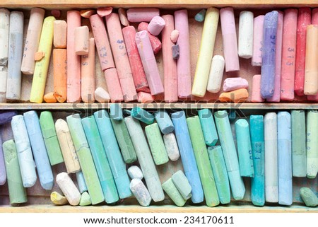 Pastel crayons in wooden artistic box closeup, top view. - stock photo