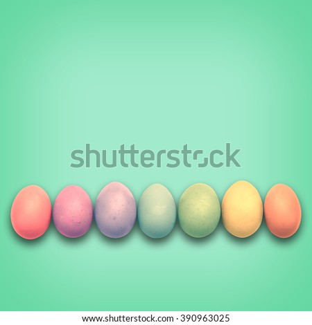 Pastel Easter eggs aligned, green background - stock photo