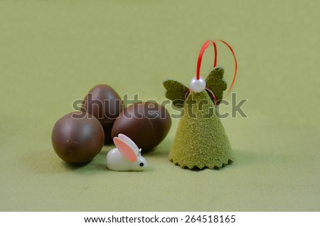 Pastel green background with handmade angel, white Easter rabbit and chocolate eggs - stock photo