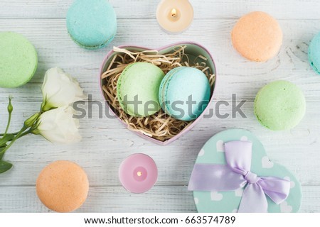 Pastel green gift box and pink bow on white rustic background. Greeting card for holidays with colorful macaroons, candles and flowers