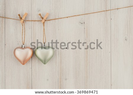 Pastel Heart hanging on the clothesline. On old wood background - stock photo