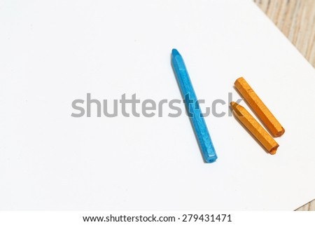 Pastel pencils blue and yellow colors on a blank sheet of paper. Space for text. The concept of drawing and design. - stock photo