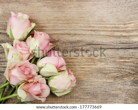 Pastel pink roses on wooden background. Copy space - stock photo