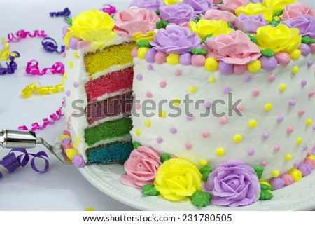 Pastel Rainbow Yellow, Pink, Purple butter cream frosting handmade roses on a round cake frosted with white icing with dots of buttercream frosting border. Sliced showing rainbow layered vanilla cake. - stock photo