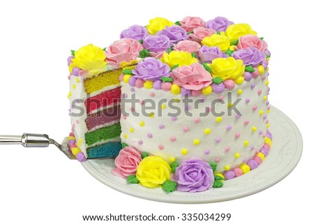 Pastel Rainbow Yellow, Pink, Purple butter cream frosting handmade roses on a round cake with dots of buttercream frosting border. Sliced showing rainbow layered vanilla cake. Isolated - stock photo