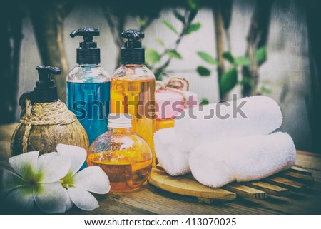 Pastel Spa oils in bottles on wooden table and nature background. - stock photo