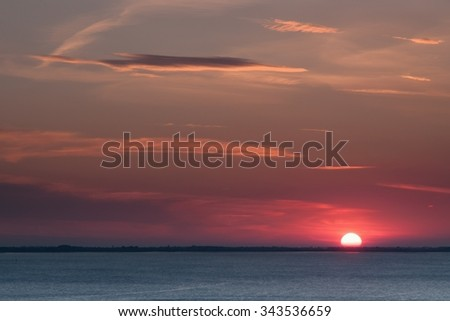 Pastel sunset over sea with dawn in sky and small colorful clouds - stock photo