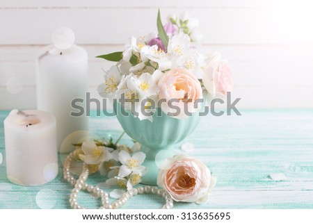 Pastel sweet roses and jasmine flowers  in vase, candles in ray of light   on turquoise wooden background. Selective focus.
