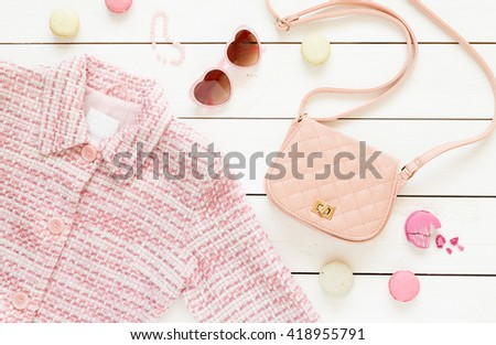 Pastel theme mood board with pink jacket and fashion accessories (bag, sunglasses) for girls. White rustic wooden background. Flat lay composition (from above, top view). - stock photo