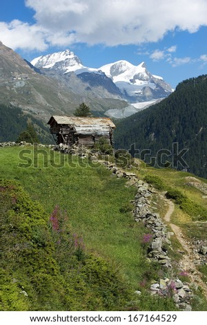 pastoral alpine landscape, wooden chalet in the Swiss Alps with views of snowy peaks - stock photo