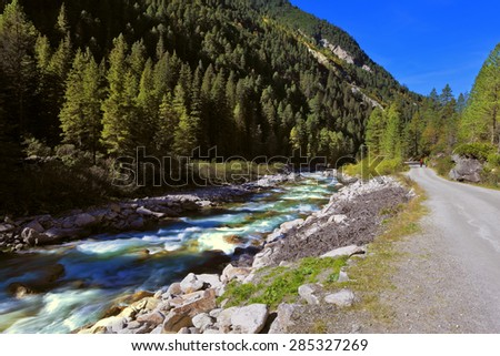 Pastoral in the Alpine mountain valley in Austria. Rapid mountain stream near the road. Cascades of cold water at the source of the famous Krimml waterfalls. - stock photo