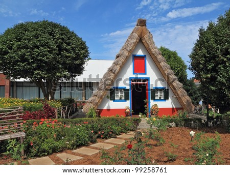 Pastoral landscape. Cosy chalet with a triangular thatched roof. Before the house - garden with beautiful flower beds. Madeira, the city of Santana - stock photo