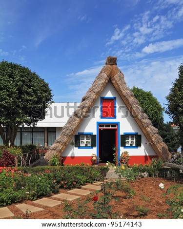 Pastoral landscape. Cozy chalet with a triangular thatched roof. Before the house - garden with beautiful flower beds. Madeira Island, the city Santana - stock photo
