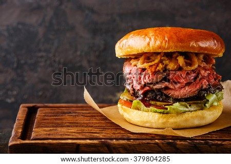 Pastrami Burger with sliced Roast beef and onion fries rings on black background - stock photo