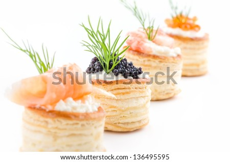Pastries with salmon, caviar and shrimp - stock photo