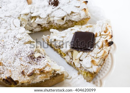 pastry cake with cream, covered with almonds and icing sugar - stock photo