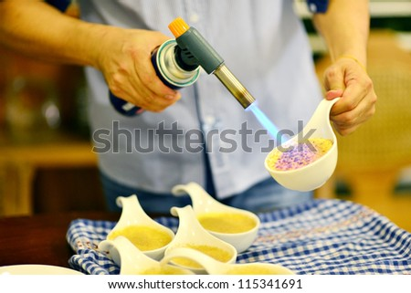 Pastry Chef caramelizing a creme brulee using a torch. - stock photo