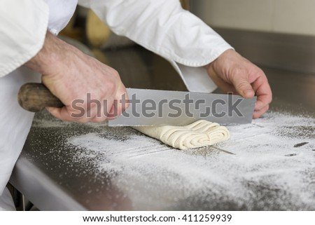 pastry chef cuts the dough for preparing cookies - stock photo