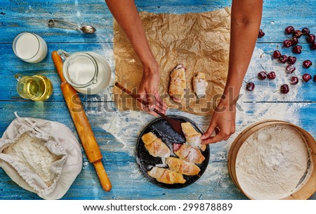 Pastry chef puts bagels on paper from the cast-iron cookware in which they bake, standing next to the milk. On the baking paper housewife posted croissants with different fillings - stock photo
