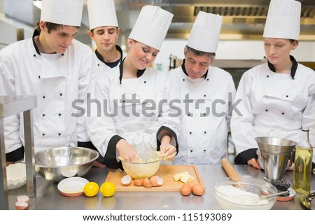 Pastry chef showing students how to prepare dough in kitchen - stock photo
