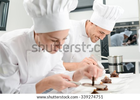 pastry cook professional team man and woman in restaurant kitchen preparing a chocolate dessert - stock photo