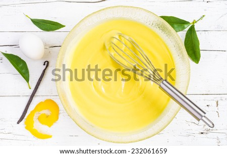 Pastry cream on white wood background. Preparation of custard pastry cream in a bowl, top view. Ingredient patisserie. - stock photo