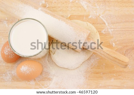 Pastry, flour, milk and eggs on wooden background