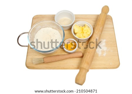 Pastry ingredients on a wooden board isolated against white - stock photo