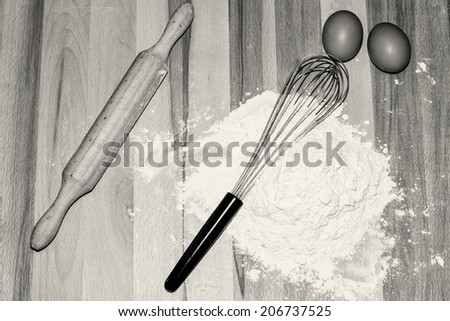 Pastry utensils: eggs, flour, whisk and rolling pin in black and white. - stock photo
