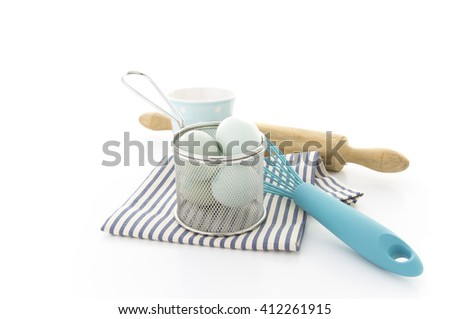 Pastry utensils with blue eggs, whisk and rolling pin on a white background with copy space - stock photo