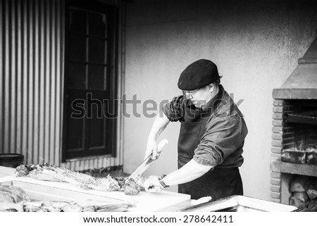 PATAGONIA, CHILE - NOV 6, 2014:  Unidentified Chilean man preapares a traditional national food of Chile Asado. Chilean people are of mixed Spanish and Amerindian descent