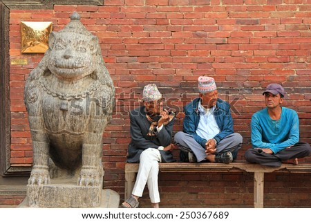 PATAN, NEPAL - APRIL 2014 : Nepalese men sitting next to a stone lion at Golden Gate, entrance to the Patan Museum in Patan, Nepal on 13 April 2014. Patan Museum is an old royal palaces. - stock photo