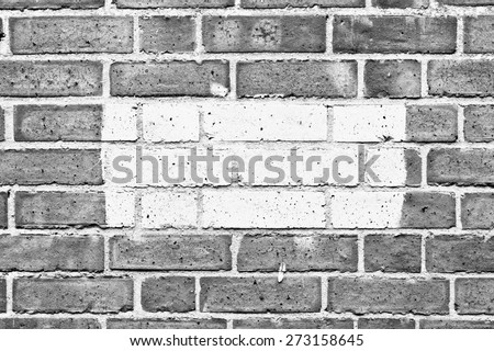 Patch of grey paint on a brick wall in black and white - stock photo