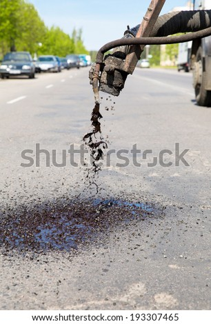 Patch Pothole Repair on Road by means bitumen and gravel - stock photo