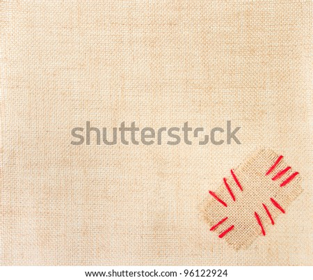 Patch with red stitch over burlap background. Sackcloth with copy space - stock photo