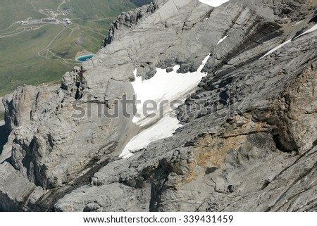 Patche of snow on the slope of Monch mountain if Alps in Jungfrau region - stock photo