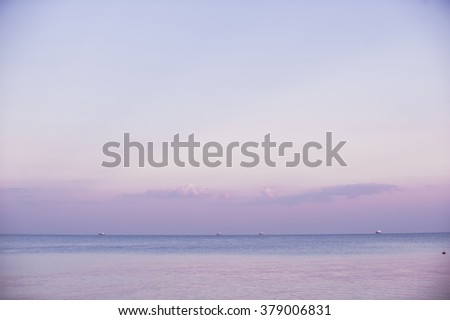 Patches of light on the sea on horizon with visible sailing vessels - stock photo